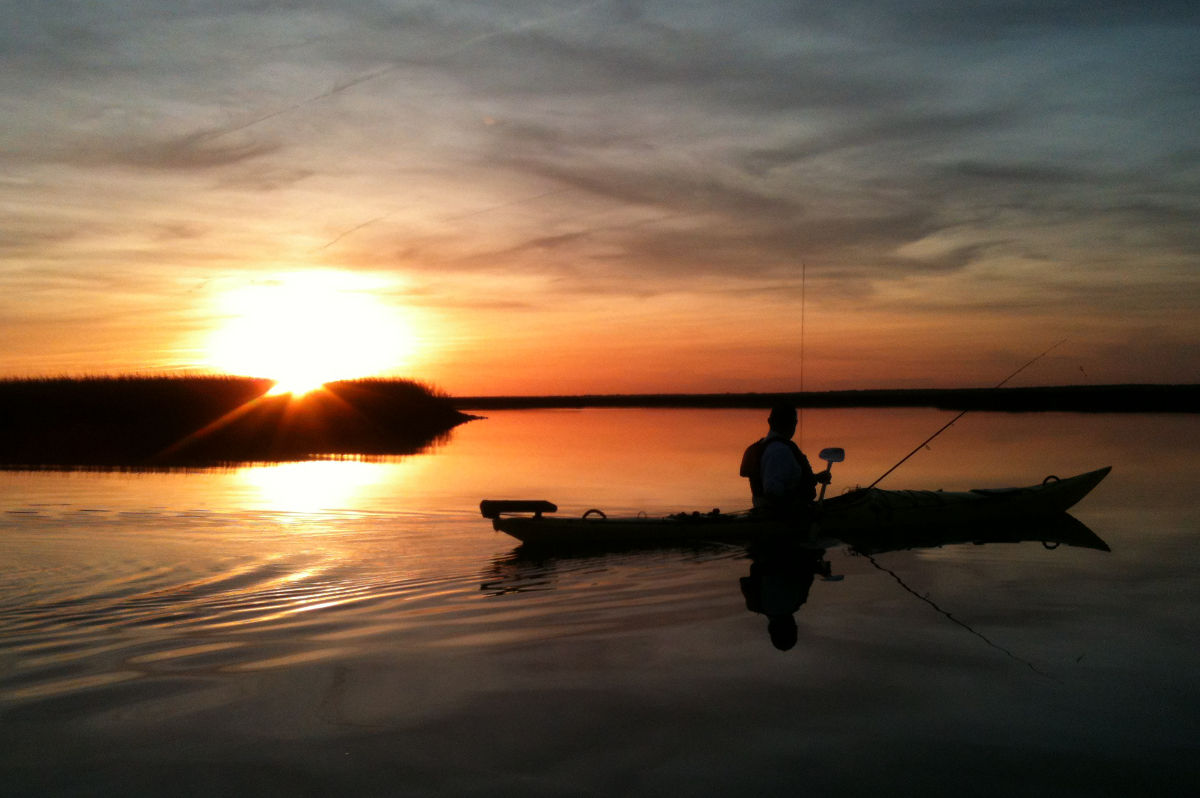 After a day of kayak fishing, a friend watches the sun set during the paddle back in over extraordinarily calm waters.